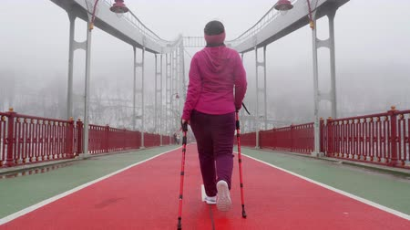 red shoes : Nordic walking. Young chubby Caucasian woman hiking with the Nordic poles. Back Follow Shot. Slow Motion Stock Footage