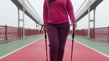 tracking : Nordic walking. Young chubby Caucasian woman hiking with the Nordic poles. Close up Front Follow Shot. Slow Motion