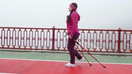 bengala : Nordic walking. Young chubby Caucasian woman hiking with the Nordic poles. Side Follow Shot.