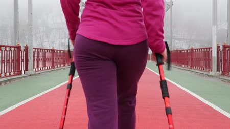 walkers : Nordic walking. Young chubby Caucasian woman hiking with the Nordic poles. Close up Back Follow Shot. Slow Motion