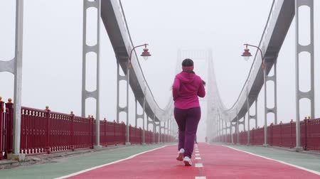 pólos : Young chubby caucasian girl running on a bridge. Back shot. Purple outfit