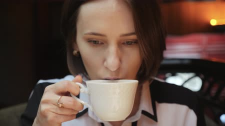 латте : Young attractive Caucasian woman is drinking coffee tea in a restaurant dressed in white shirt