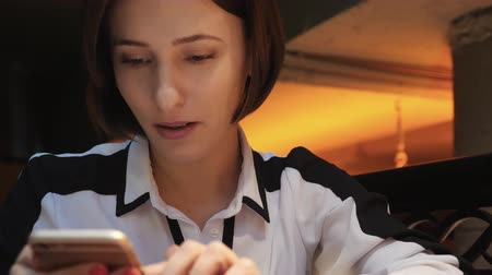 hosenträger : Young Attractive woman uses her mobile phone in a cozy cafe restaurant. She is surprised and angry.