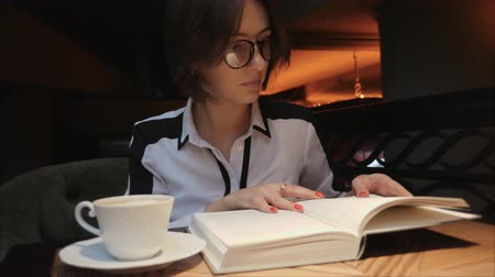 страница : Young woman in glasses opening and reading a book while drinking coffee in cozy cafe. Business lady reading a book