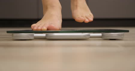 tartmak : Human barefoot measuring body weight or overweight on kitchen. Woman on scales measuring weight. Weight loss concept Stok Video