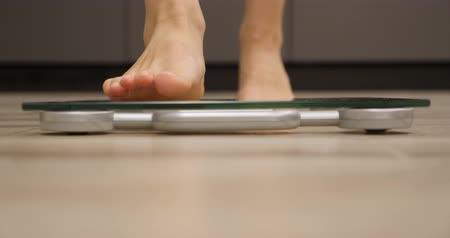 gevşek : Human feet are standing on scales, close up. Woman on scales measuring weight. Weight loss concept Stok Video