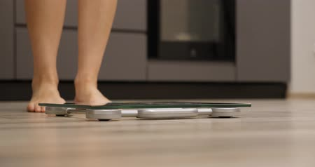 wegen : Female feet standing on weighing scales in room. Woman legs step on scale. Human on scales measuring weight. Weight loss concept