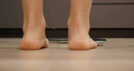 tartmak : Female barefoot stand on weighing scale in kitchen. Human legs measuring body weight, close up. Girl feet checking weight. Weight loss concept.