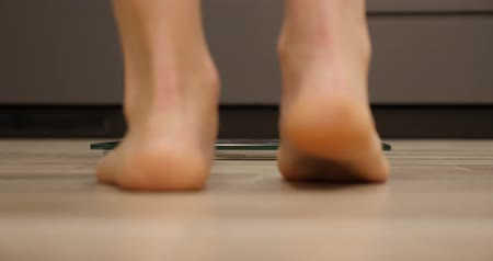 gevşek : Girl feet standing on weighing scale. Woman on scales. Female checking weight or overweight, close up, backside view Stok Video