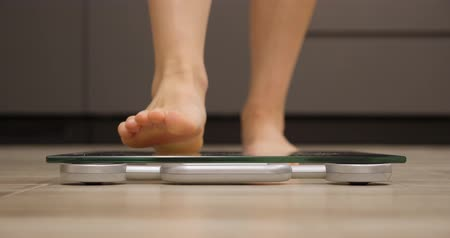tartmak : Woman steps on weighing scales. Female feet checking body weight in kitchen. Human legs measuring weight, close up view