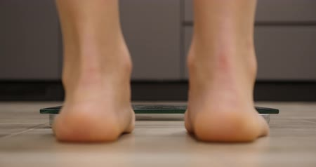 gevşek : Woman on scales. Female stepping on weighing scales. Feet measuring body weight or overweight, close up. Legs checking body weight