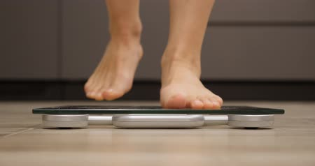 wegen : Female feet step on weighing scales. Woman checking body weight in room. Girl standing on scales. Weight loss concept