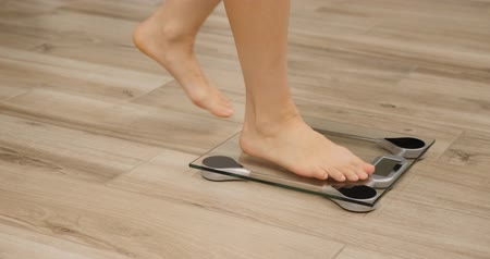 tartmak : Human barefoot steps on body weight scales. Woman checking weight on scale in room. Girl measuring overweight
