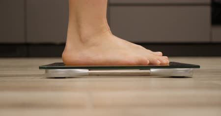 tartmak : Woman on body scales. Girl barefoot checking weight, close up, side view. Female feet measuring overweight Stok Video