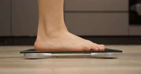 gevşek : Feet stepping on weighing scales. Female barefoot measuring body weight in kitchen. Woman checking weight. Human legs on scales Stok Video