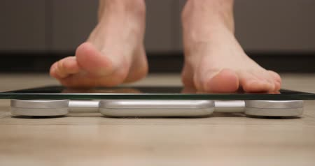 wegen : Man barefoot steps on weighing scales. Male feet measuring body weight. Human standing on scales, close up, front view Stockvideo