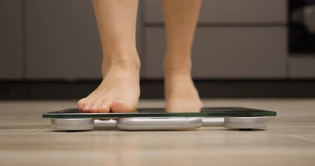 gevşek : Woman barefoot steps on scales. Female feet measuring body weight. Human legs on weighing scales in room. Girl checking her weight Stok Video