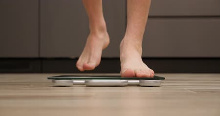 tartmak : Male checking body weight on scales in kitchen. Man feet on weighing scales. Boy legs measuring weight, close up