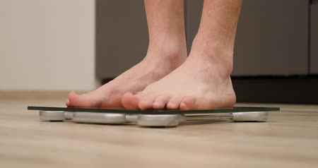 tartmak : Man feet step on weighing scales. Male on scales. Human measuring body weight in kitchen. Legs on scales, close up