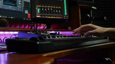 compresor : Professional musician playing on electric piano midi keyboard in recording music studio. Male hands plays piano in home music studio with monitors and equalizer mixing gear on screen