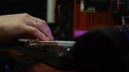 compresor : Close up of male hands playing on electric piano midi keyboard in home music studio. Fingers plays piano in recording studio. Sound composer creating romantic song