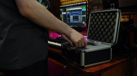 compresor : Sound engineer takes out microphone from box. Male hands taking out professional microphone at home recording music studio. Digital audio workstation
