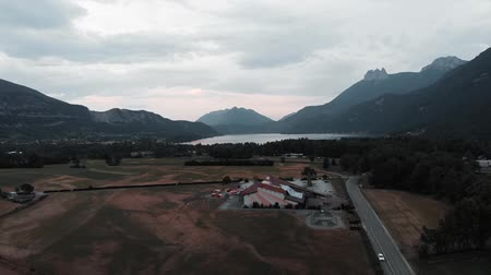 snow on grass : Incredible mountains and lake from bird eye view. Drone shot of lake Annecy and Alps in France. Field of hang gliding center Stock Footage