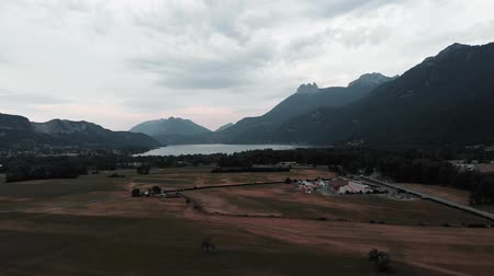 snow on grass : Mountain lake surrounded by Alps mountains, drone view. Doussard commune in France with Annecy lake on background. Drone flying in Alps