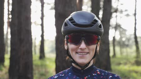 aparat ortodontyczny : Portrait of young attractive cycling woman wearing black helmet and glasses and smiling. Cycling Concept