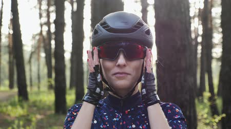 jarse : Young beautiful girl puts on cycling glasses wearing helmet and blue jersey. Road cycling concept. Slow motion
