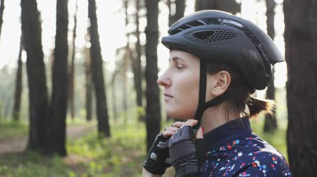 bikers : Young cute triathlete puts on black cycling helmet. Happy cyclist portrait. Triathlon concept. Slow motion