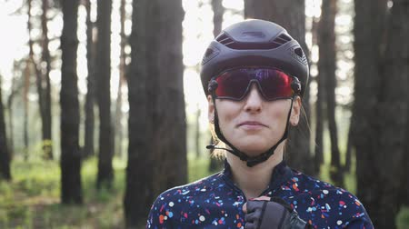 védősisak : Happy cycling girl zips in blue jersey before training wearing black helmet and glasses. Cycling concept