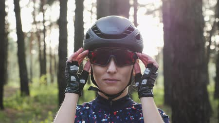 védősisak : Attractive young caucasian woman puts off cycling glasses wearing black helmet and jersey. Triathlon concept. Slow motion Stock mozgókép