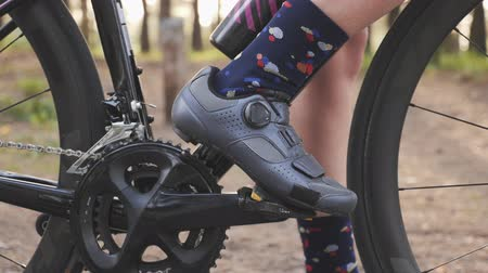 braces : Cycling shoe clips in pedals. Cycling concept. Chainring and bike wheel close up. Slow motion Stock Footage