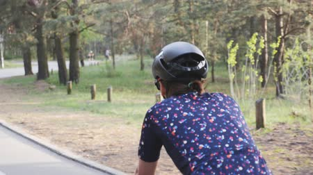 braquets : Close up shot of female cycling riding bike in a park wearing black helmet and blue jersey.