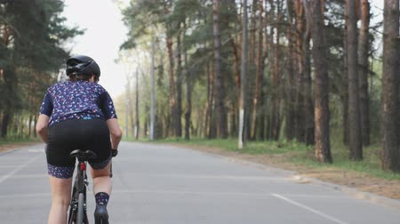 braces : Female cute cyclist rides a bicycle in the park as a part of her training routine. Cycling concept. Slow motion