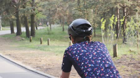 braces : Close up shot of female cycling riding bike in a park wearing black helmet and blue jersey. Slow motion