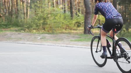 braces : Sportive fit female cyclist pedalling out of the saddle in the park. Hard training on bicycle. Road cycling concept. Slow motion Stock Footage