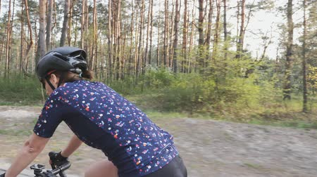 braces : Female cyclist riding a bicycle in the park. Side follow shot. Cycling training Stock Footage