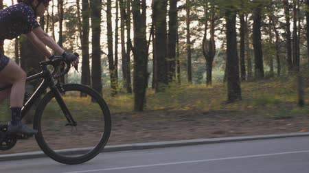 aparat ortodontyczny : Female cyclist riding road bicycle in the park with the sun shining through trees. Cinematic cycling concept. Slow motion