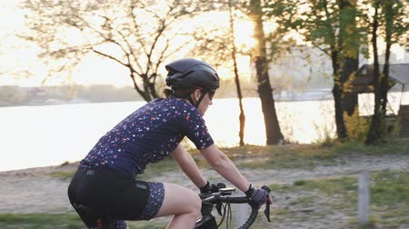 braces : Young female riding bicycle with river, city and sunset on the background. Cycling concept. Slow motion Stock Footage