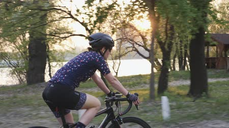 braces : Fit sportive female cyclist on a bicycle in the city park before sunset. Cycling concept. Slow motion