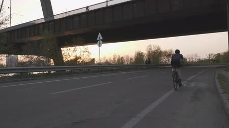 braquets : Girl riding a bicycle out of the sadle towards the bridge on sunset.