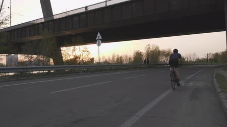 braces : Girl riding a bicycle out of the sadle towards the bridge on sunset. Slow motion