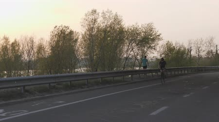 aparat ortodontyczny : Female cyclist riding towards camera at sunset. Cinematic cycling concept. Slow motion Wideo