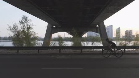 guidon : Silhouette of female cyclist riding a bicycle at sunset under the bridge. Cinematic cycling shot. Slow motion Vidéos Libres De Droits