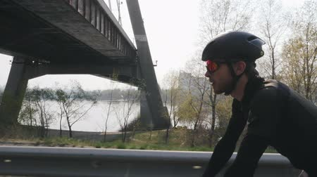 ciclismo : Focused confident cyclist on a bicycle. Sun shines through. River and bridge in background. Close up side view. Cycling concept.