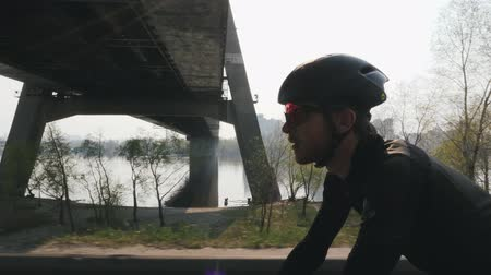 cadeia : Close up shot of cyclist on a bicycle. Bearded cyclist wearing black helmet and sunglasses riding bicycle with bridge and river on the background. Slow motion