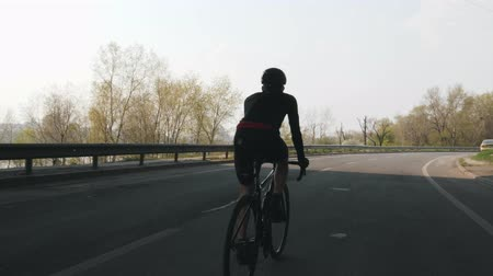 carbono : Confident triathlete riding bicycle. Triathlon training. Follow shot of cyclist pedaling on bicycle.