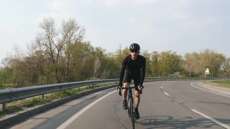 jarse : Focused Cyclist on a road bicycle riding towards camera at sunset. Biker wearing black jersey and shorts. Cycling concept. Stok Video